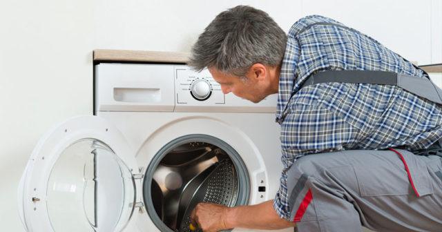 Мужчина ремонтирует стиральную мшинку
