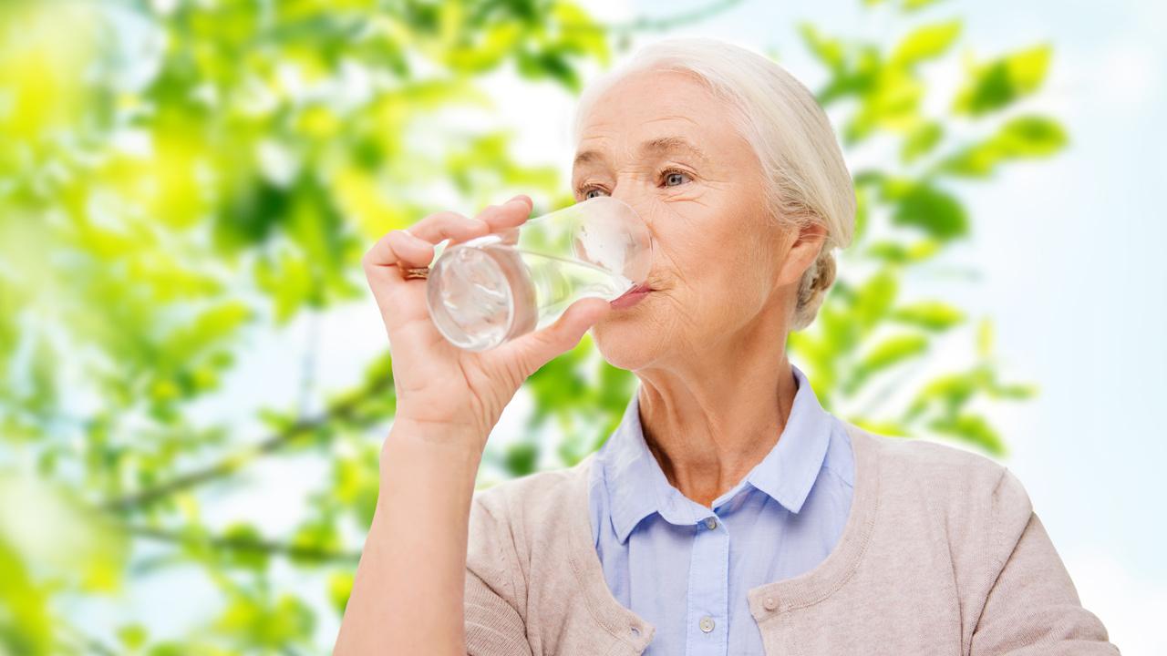 пожилой человек пьет воду